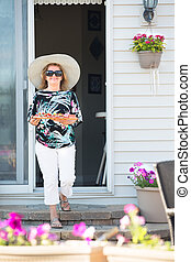 Blonde lady with large brim hat coming out from house with a...