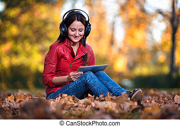 Girl Listening Music In The Autumn Sunshine - Young Woman...