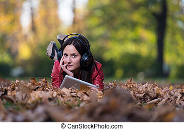 Young Woman Lying Outside And Listening To Headphones -...