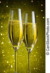 two champagne flutes with golden bubbles on yellow light...