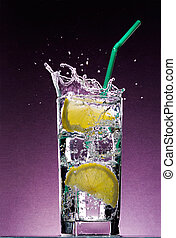 sliced lemon falling in glass of alcoholic drink with ice cubes and green straw on textured violet background
