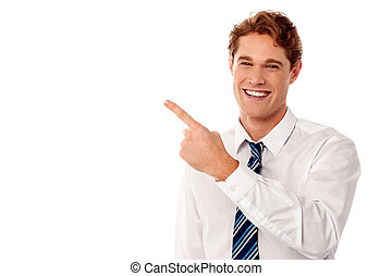 Smiling businessman pointing away