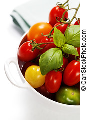 Assorted tomatoes and vegetables in colander - Assorted...