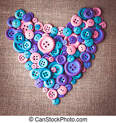 Heart shape from buttons over canvas textile