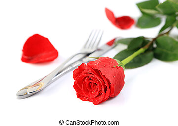 Beautiful red rose with a setting with knife and fork on a...