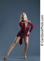 Elegant young blond woman dancing in studio, on gray...