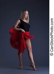 Pretty sensual woman dancing with red cloth in studio
