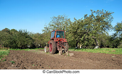 ploughing field on old tractor in Ukraine