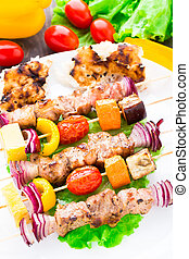 Barbecued pork and vegetable kebabs on a plate