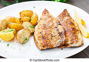 Fried mackerel with baked potato on a plate