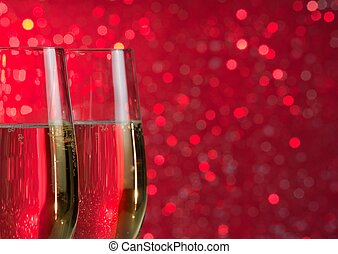 pair of a champagne flutes on red light bokeh background -...