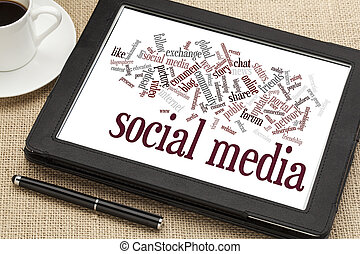 social media word cloud on a digital tablet with a cup of...