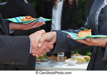 Business handshake during lunch on the open air