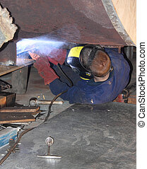 Welding - A welder welding a new support in position on an...