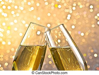 detail of a champagne flutes with golden bubbles on light...