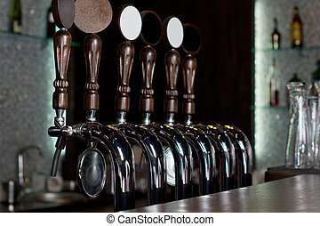 Row of beer taps on a stainless steel keg in a pub - View...