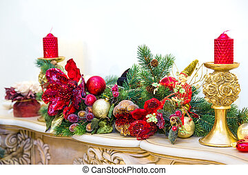 Fireplace mantle decorated with candles and garlands for...
