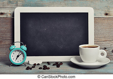Cup of coffee with blackboard and alarm clock on vintage...
