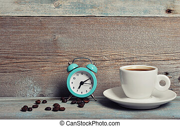 Cup of coffee with alarm clock on vintage wooden background