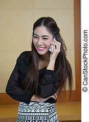 Young business woman speaking mobile phone with sweet smile.