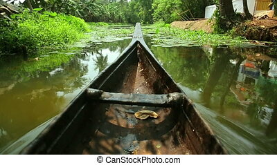Boat moving along canal at sunset in Kerala Backwaters