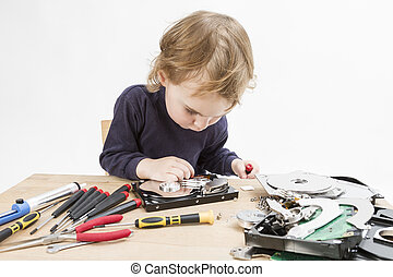 child repairing hard disk drive - young child repairing open...