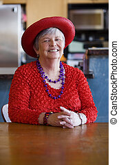 Senior Woman Wearing Red Hat - Friendly senior woman wearing...