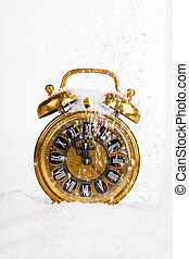 Antique gold clock in the snow. with copy space on a white...