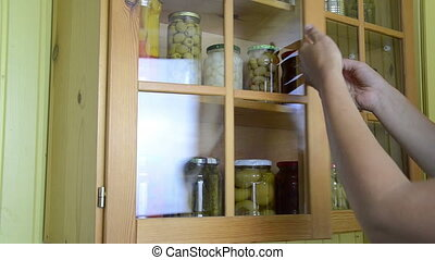 jar shelf - hand opens a wooden cupboards door and take all...