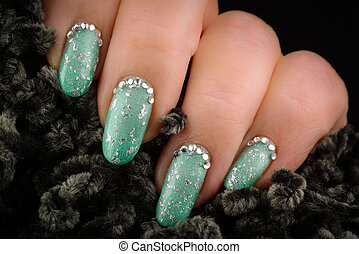 Green nails with glitter and rhinestones on a dark...