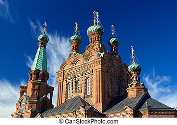 Top towers of Tampere Orthodox Church with blue sky and...