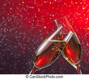 champagne flutes with gold bubbles on red and violet light...