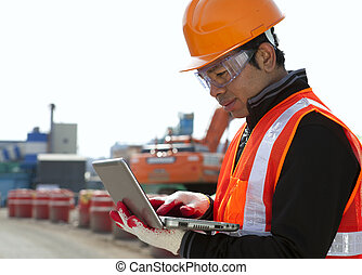 Construction worker using laptop with excavator on the...