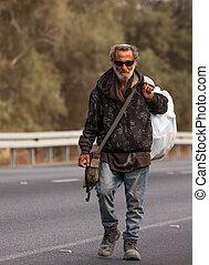 Bedouin - poor Bedouin walking on the road summer day