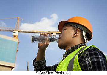 Construction worker - Tired construction worker drinking...
