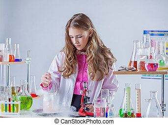 Image of young scientist stirs reagent in flask, close-up