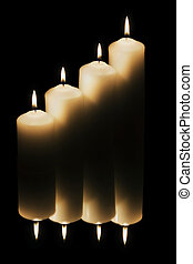 Four candles reflected on dark back