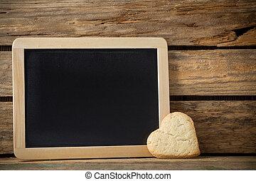 Blackboard. - Blackboard on wooden background with heart...