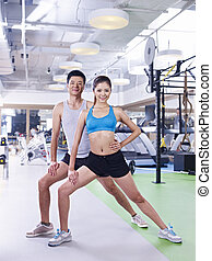 man and woman exercising in gym - young asian man and woman...