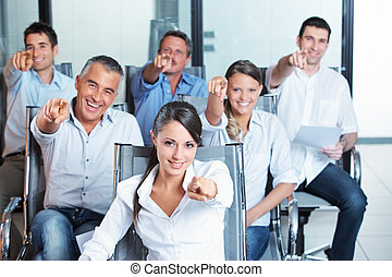 We need you! - Portrait of a smiling business team pointing...