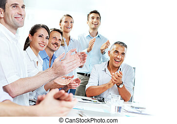 Business people clapping in a meeting - A group of happy...