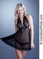 Studio shot of smiling attractive blonde woman in erotic...