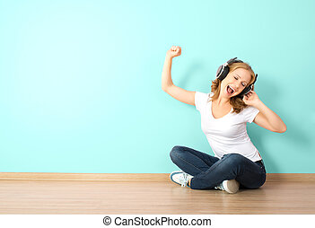 happy young woman in headphones listening to music in a room with a blank wall