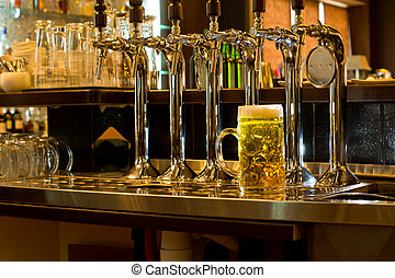 Row of beer taps in a pub with a tankard of beer - Row of...