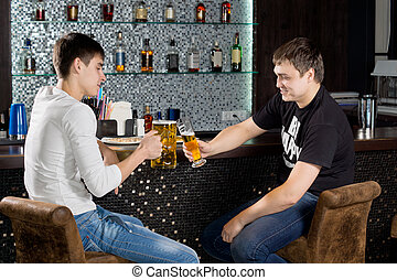 Two male teenagers sitting at the bar, toasting - Two happy...