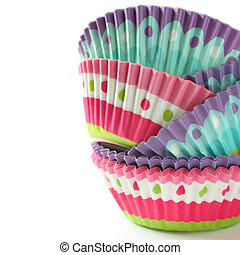 Colorful cupcake wrappers over white  with copyspace