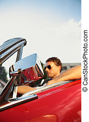 Road trip - Handsome man driving a convertible car, focus on...