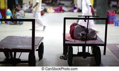 Man sleeping on push cart - Everyday scene with man sleeping...