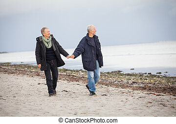 mature happy couple walking on beach in autumn lifestyle...