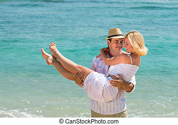 Happy young couple enjoying at beach - Happy young man carry...